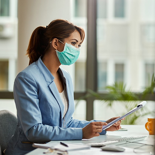 Businesswoman wearing face mask while analzying reports in the office.